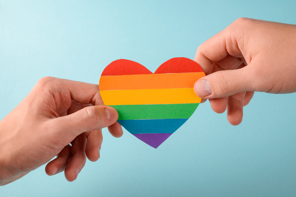 Two,Guys,Holding,A,Paper,Heart,With,Lgbt,Flag.,St.