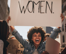Laughing,Young,Woman,Holding,A,Banner,During,A,Protest.,Group